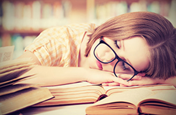 Fatigued woman sleeping on books